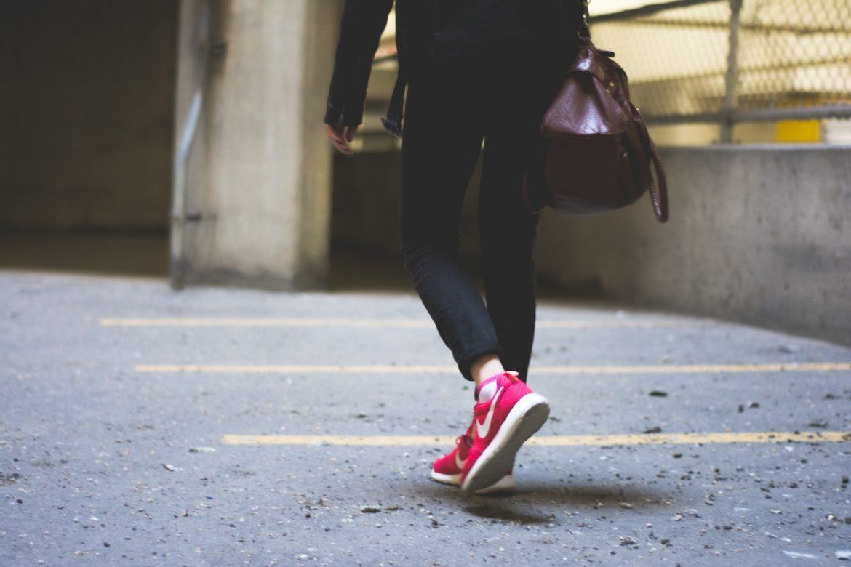 Kobieta, chodzenie, sportowe buty i torba do pracy